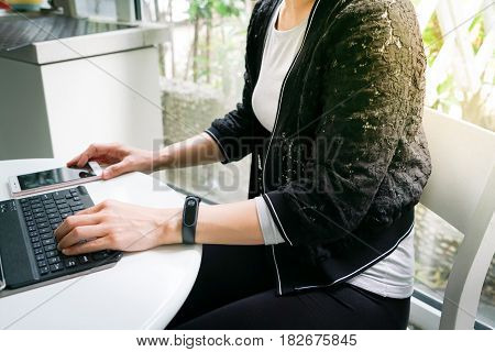 Young student women wearing smart band using tablet computer and touching smart phone