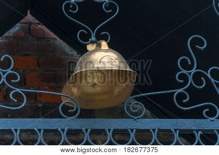 Vintage bronze fireman's hat on a dark background hanging on the metal patterns of the wire.