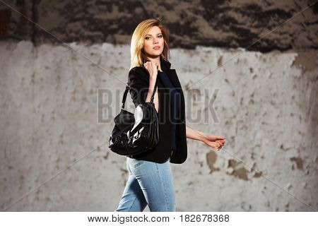 Young fashion blond business woman with handbag walking in city street