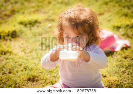 Portrait of a baby girl with a bottle in park