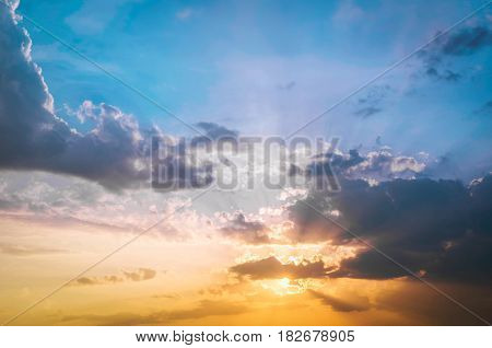 Golden light shining through the clouds in a colorful evening at sunset and blue sky