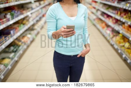 consumerism, shopping, technology and people concept - close up of woman with smartphone at shop or supermarket