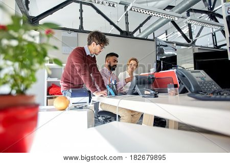 business, startup and people concept - international creative team with tablet pc computers in office