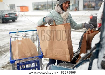 consumerism, transportation and people concept - woman loading food from shopping cart to car trunk at winter parking