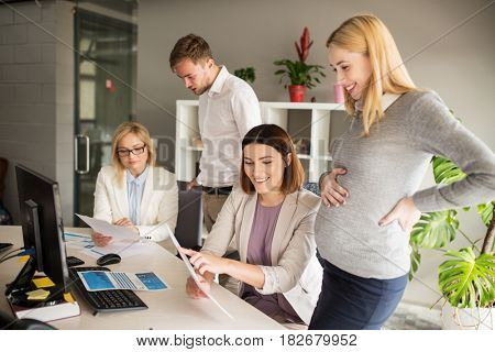 pregnancy and people concept - happy business team with papers in office