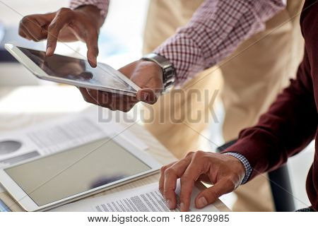 business, technology and people concept - businessmen with tablet pc computer and papers at office