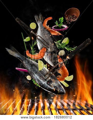 Flying raw whole bream fish and prawns, with ingredients for cooking above grill fire. Freeze motion of cooking staff. Fork holding the meat. Concept of food preparation in low gravity mode.