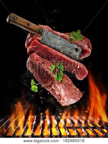 Flying raw steaks with meat cleaver, barbecue grill with fire flames. Concept of food preparation in low gravity mode. Separated on black background