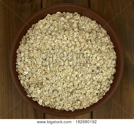Dry oat flakes oatmeal in bowl on wooden table