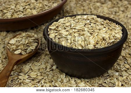 Dry oat flakes oatmeal in bowls on the background with wooden spoon