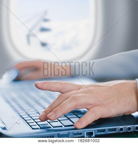 Passenger using laptop in airplane