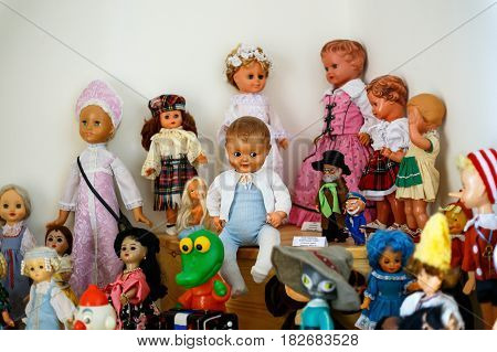 Dolls, toy figures of fairy-tale heroes, soft toys, puzzles, designers on shelves in a toy store