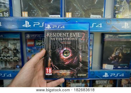 Bratislava, Slovakia, circa april 2017: Man holding Resident Evil Revelations 2 videogame on Sony Playstation 4 console in store