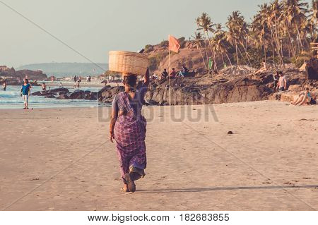 Goa, India - March 4: Woman In Saris With Basket On Her Head Walks By Vagator Beach On March 4, 2017
