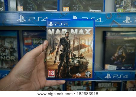 Bratislava, Slovakia, circa april 2017: Man holding Mad Max videogame on Sony Playstation 4 console in store