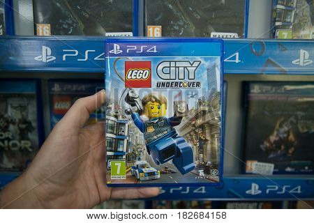 Bratislava, Slovakia, circa april 2017: Man holding Lego City Undercover videogame on Sony Playstation 4 console in store
