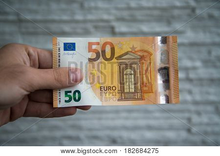 Man holding new 50 euro banknote