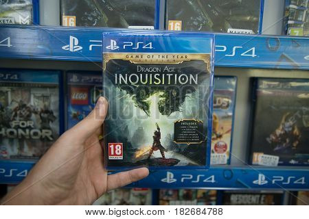 Bratislava, Slovakia, circa april 2017: Man holding Dragon Age Inquisition videogame on Sony Playstation 4 console in store