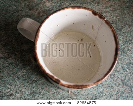A Small White And Black Spotted Cup With A Rusty Rim And With A Small Bit Of Liquid, Water, And Oil