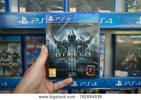 Bratislava, Slovakia, circa april 2017: Man holding Diablo 3 Reaper of Souls Ultimate Evil Edition videogame on Sony Playstation 4 console in store
