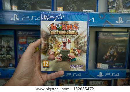 Bratislava, Slovakia, circa april 2017: Man holding Worms Battlegrounds videogame on Sony Playstation 4 console in store