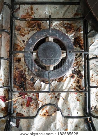 The Dirty And Grimy And Rusted Top Of Gas Cooker Hob With Bits Of Foil Underneath The Metal With Bit