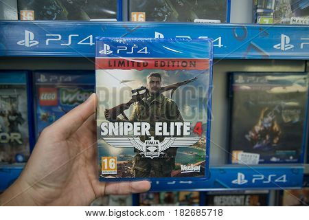 Bratislava, Slovakia, circa april 2017: Man holding Sniper Elite 4 Italia videogame on Sony Playstation 4 console in store
