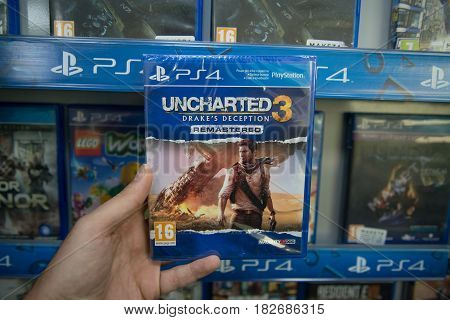 Bratislava, Slovakia, circa april 2017: Man holding Uncharted 3 Drake's Deception videogame on Sony Playstation 4 console in store