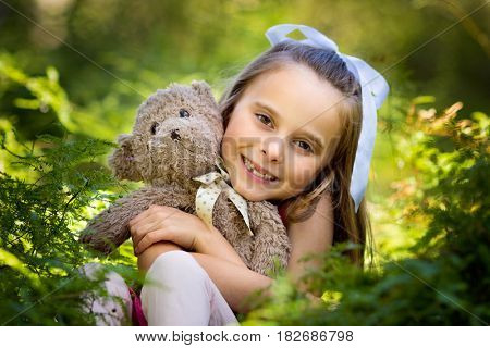 Pretty smiling girl holding teddy bear