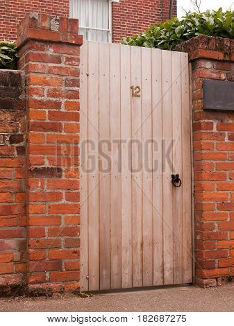 A Wooden Door Outside Closed With The Number 12 On It And Attached To A High Wall On A House