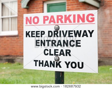 A Sign Outside A House Saying No Parking Keep Driveway Entrance Clear Thank You Red And White And Bl