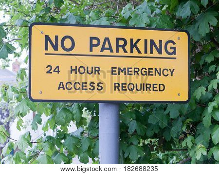 A Yellow No Parking 24 Hour Emergency Access Required Post Metal Sign Outside Near Car Par Restricti