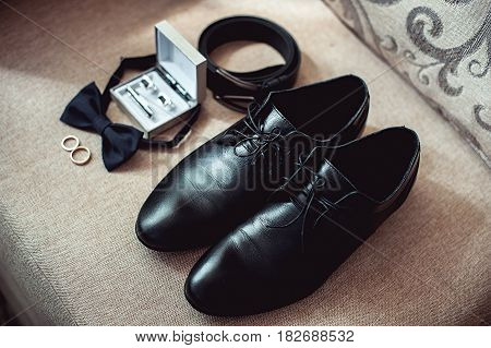 Close up of modern man accessories. wedding rings, black bowtie, leather shoes, belt and cufflinks. Selective focus.