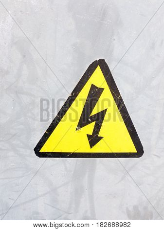 A Safety Sign Yellow And Black On Silver Metal Background Electric Bolt In Triangle Safety Caution C