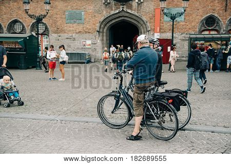 Bruges Belgium - July 29 2016: Cyclists in Markt Square in the city of Bruges. The historic city centre is a World Heritage Site of UNESCO. It is known for his picturesque cobbled lanes and dreamy canals