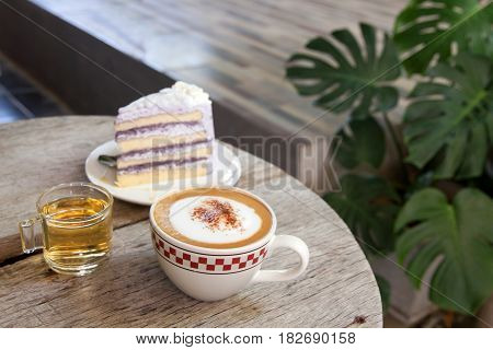 Coffee Break taro cake and Cappuccino coffee on wood table