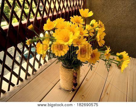 Flowers, a bouquet of yellow chamomiles on the veranda, daylight.