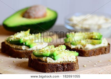 Homemade chickpeas hummus and avocado sandwiches on a wooden board, avocado half, hummus in a glass bowl. Vegetarian open sandwiches made with rye bread, avocado slices, hummus and fried sesame seeds