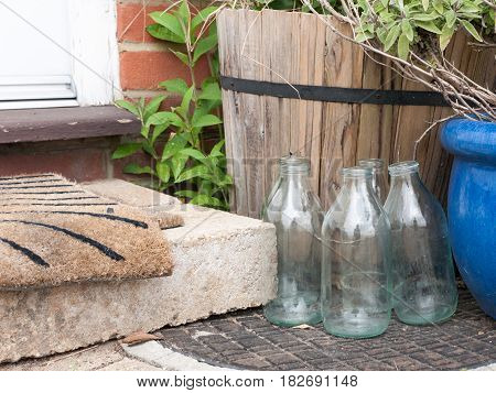 Close Up Cool And Modern Shot Of Some Glass Milk Bottles Glasses Outside Empty No Milk Next To Front