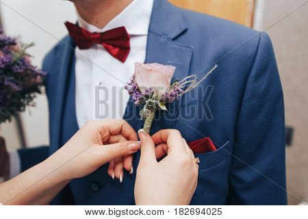 the bride is wearing a beautiful boutonniere on suit jacket of groom