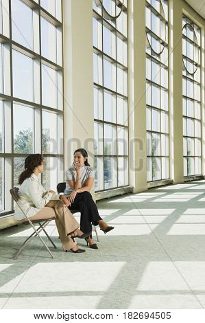 Businesswomen talking in office lobby