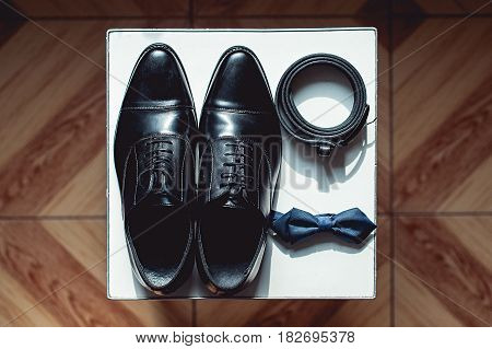 Close up of modern man accessories. black bowtie, leather shoes, and belt on a square white stool. Wedding morning
