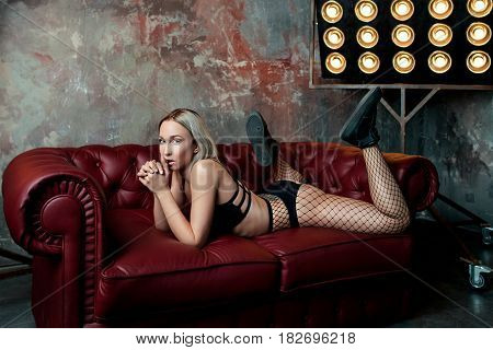 Stylish  Blonde attractive pretty woman dancer in lingerie and sneakers on red leather sofa
