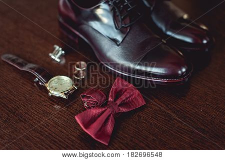 Close up of modern man accessories. wedding rings, cherry bowtie, leather shoes, watch and cufflinks on the brown wooden table. Selective focus. groom's morning preparation