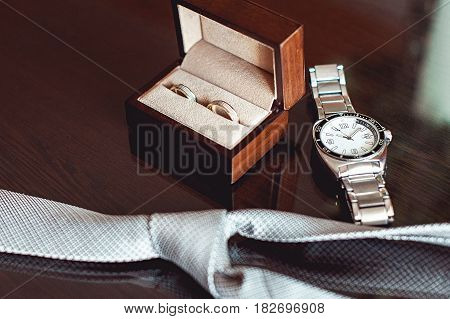 Close up of modern groom accessories. wedding rings in a brown wooden box, necktie and watch. Selective focus.