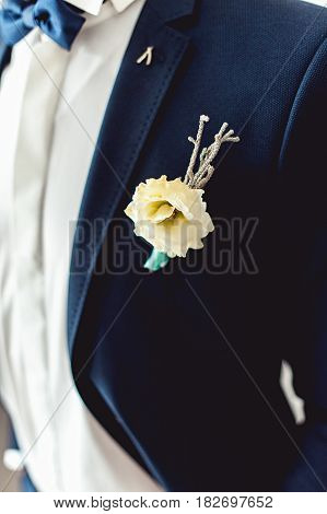 Details of male wedding clothes. Close up of white flower corsage. Beautiful boutonniere pinned on man in blue suit, white shirt and blue bow tie.