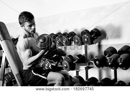Horizontal monochrome shot of a handsome young athletic man with muscular fit and toned body flexing his muscles using dumbbells at the gym copyspace bodybuilder sportsman athlete concept.