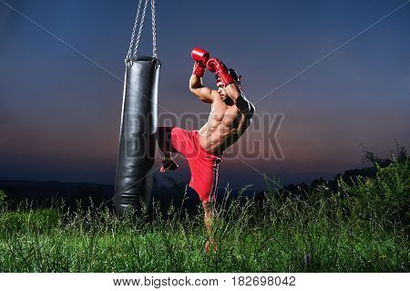 Handsome shirtless muscular young kick boxer working out with a punching bag outdoors copyspace beautiful sunset on the background nature lifestyle sports active athlete athletic masculinity training.