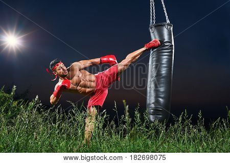 Horizontal shot of a kick boxer working out with a punching bag outdoors at night copyspace kicking training sports sportive motivation fitness muscles toning fit ripped strong lifestyle professional.