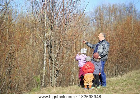 GOMEL BELARUS - 9 April 2017: A man in nature tells the children about the spring.